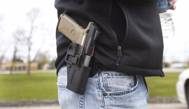 A gun rights supporter carries his Ruger model SR9 pistol on his hip during a ra