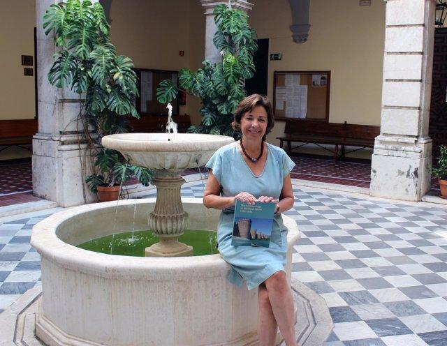 Magdalena Valor en una fuente posando con el libro