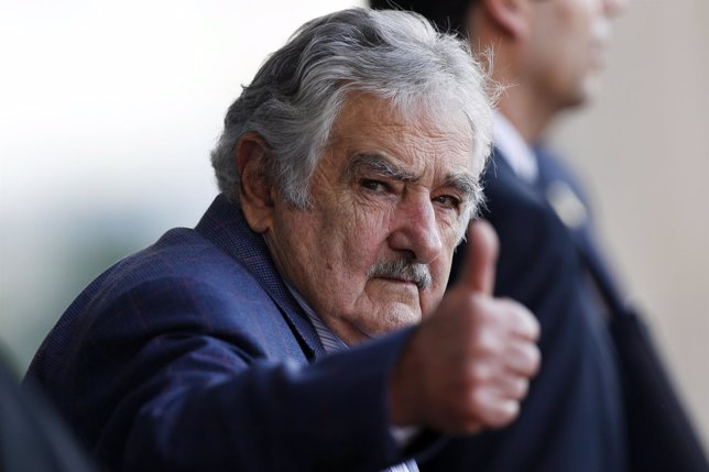 Uruguay's President Jose Mujica waves as he leaves the Itamaraty Palce after the