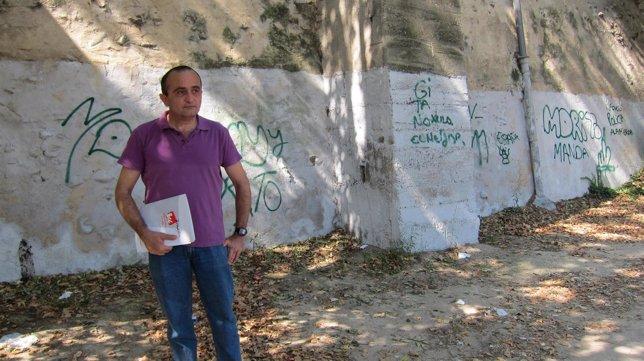 El concejal de IU, Raúl Ariza, delante de una pintada en la ribera del Ebro