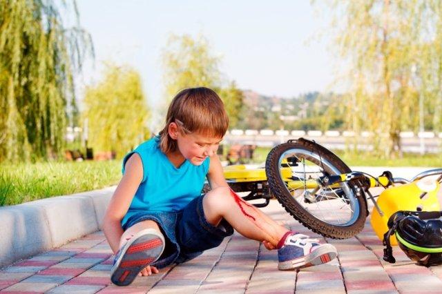 Primeros auxilios en el parque infantil, herida, niño, bicicleta