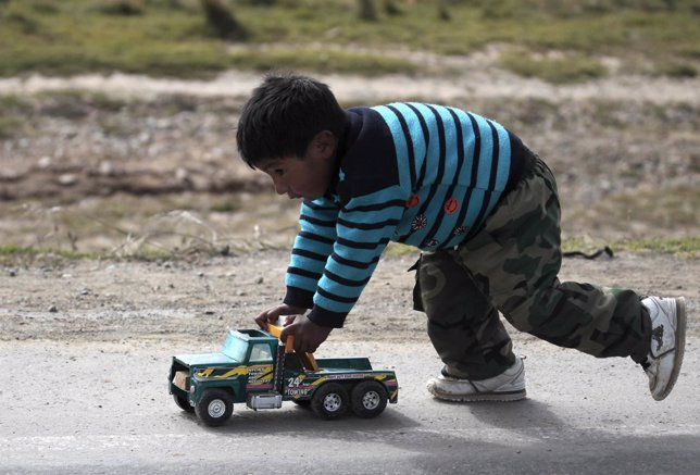 A child plays with a toy car along the La Paz-Oruro highway