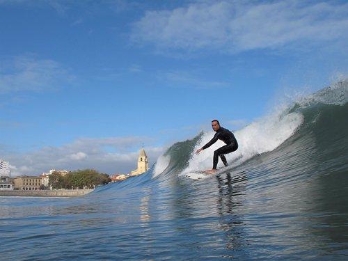 Un surfista en la playa San Lorenzo de Gijón.