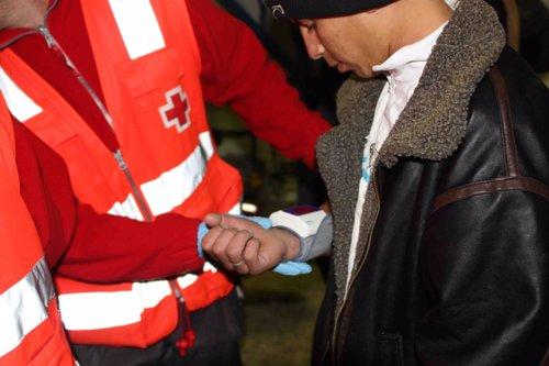 Un voluntario atiende a un inmigrante acabado de llegar