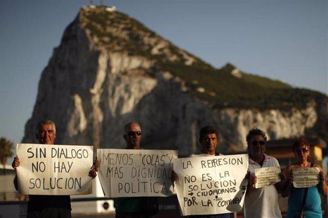 Trabajadores españoles posan para una fotografía mientras sostienen letreros fre