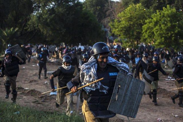 Policías perseguidos por manifestantes opositores en Islamabad