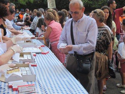 Miles de vallisoletanos se dan cita en la Acera Recoletos para catar una de las 6.500 raciones del postre de San Lorenzo