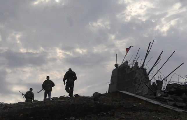 Pro-Russian separatists walk at a destroyed war memorial on Savur-Mohyla, a hill