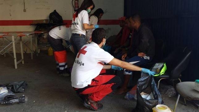 Miembros de la Cruz Roja atienden a inmigrantes llegados a España en una patera