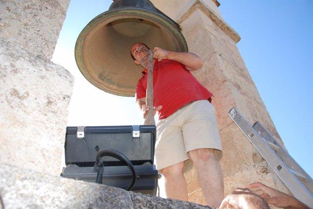 Un operario instala el badajo en la campana de la Vela de la Alcazaba