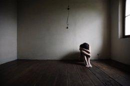 Mujer con depresión en habitación vacia