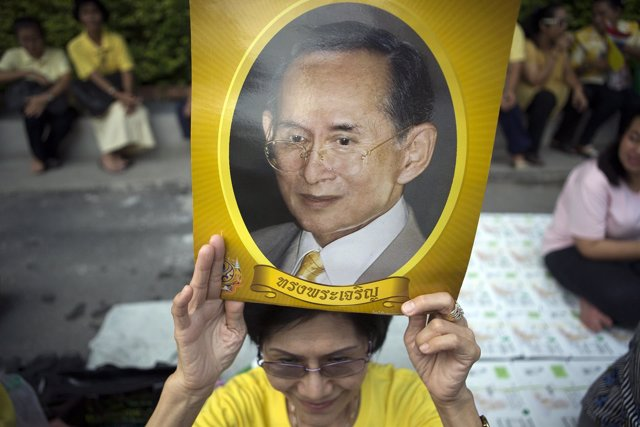 Una señora espera pide por la recuperación del rey tailandés frente al hospital