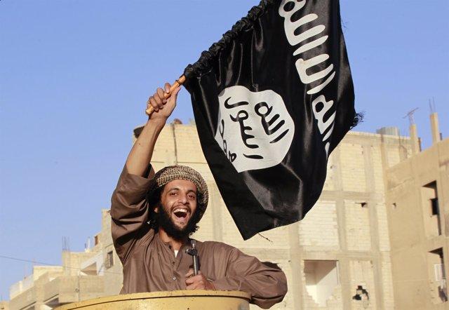 Miliciano islamista yihadista ondeando una bandera del Estado Islámico
