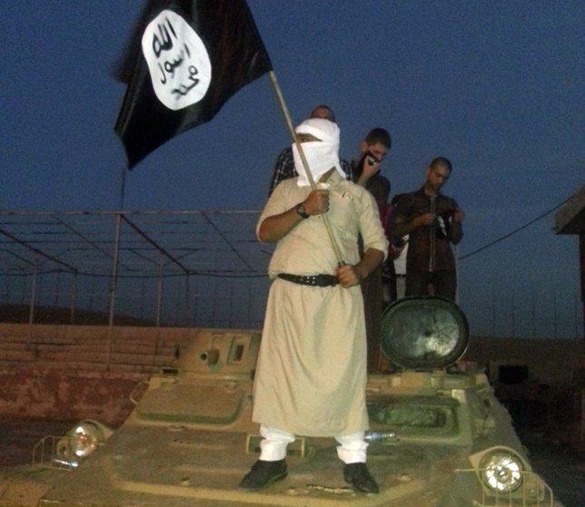 Miliciano con una bandera del Estado Islámico