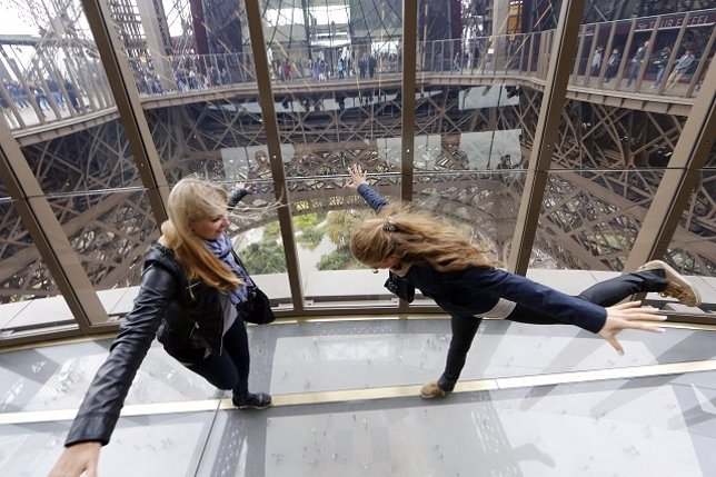 Visitors walk on the new glass floor at the Eiffel Tower in Paris