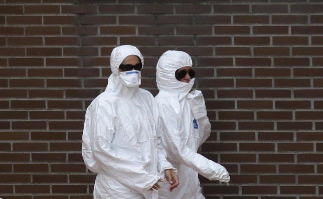 Trabajadores cerca de la casa de la enferma con ébola
