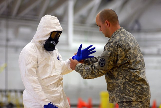 Un militar estadounidense ayuda a otro a ponerse un traje contra el ébola
