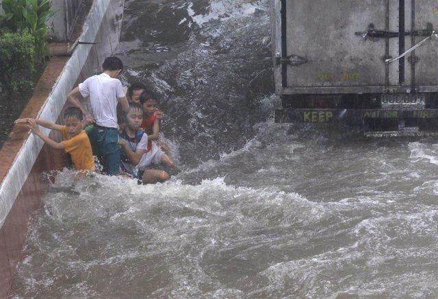 Niños en Manila tras el paso de una tormenta tropical