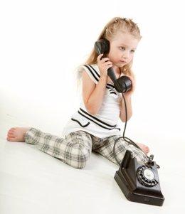 Niña sentada, teléfono, piernas en W