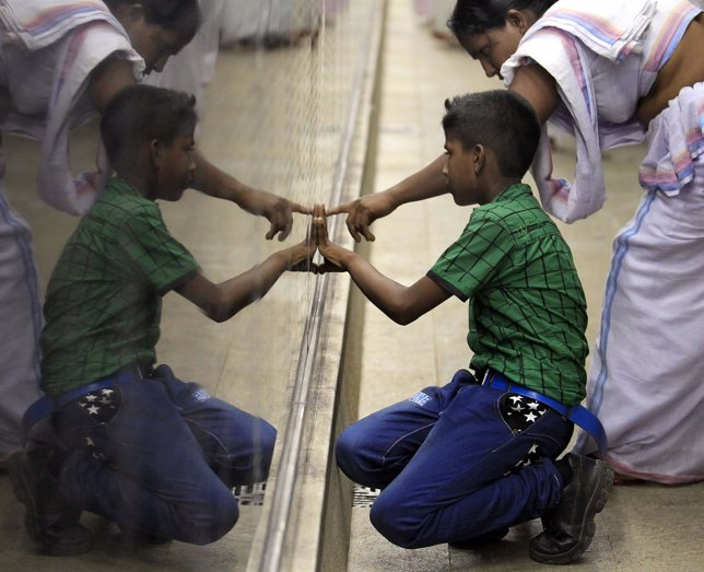 Una madre muestra a su hijo el nombre de su padre en un memorial en Sri Lanka.
