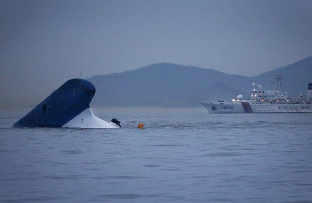 Un barco de la Guardia Costera pasa cerca del ferry surcoreano Sewol