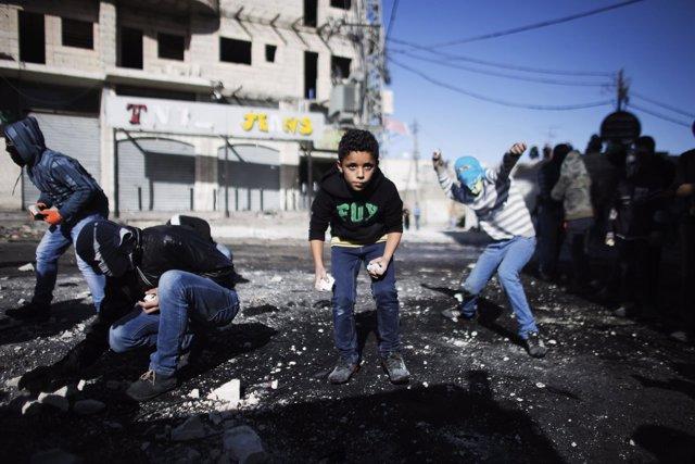 Jóvenes palestinos lanzan piedras contra policías israelíes