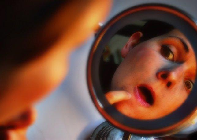 Mujer acné, marcas en la piel, espejo