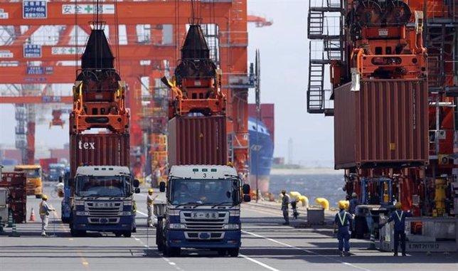 Trabajadores cargan contenedores en una embarcación en el puerto de Tokio
