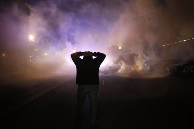 A protester stands with his hands on his head as a cloud of tear gas approaches