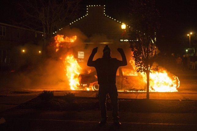 Un hombre contempla un coche de Policía arder en Ferguson durante los disturbios