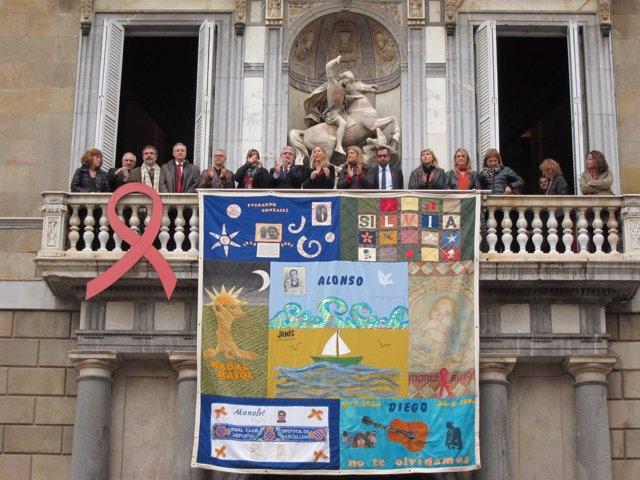 Despliegue del tapiz conmemorativo del Día Mundial del Sida en la Generalitat