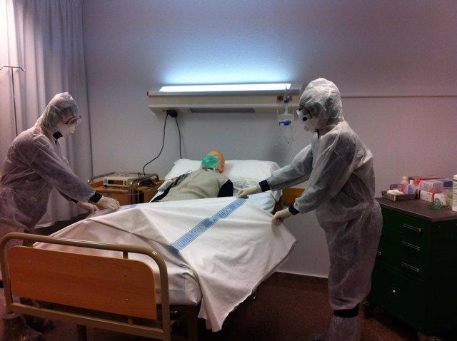 Dos profesionales con el traje explican cómo trabajar con un paciente con ébola