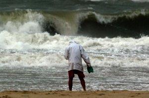 Un hombre frente a una ola generada por un tifón.