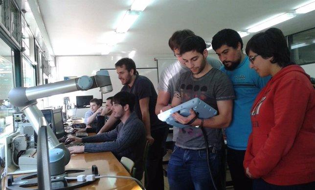 Un grupo de alumnos maneja el robot colaborativo instalado en el centro.
