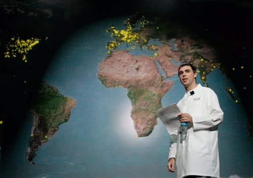 Google co-founder Larry Page walks by map of world during keynote speech at Cons