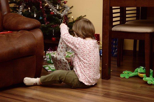 Niña abriendo regalos en Navidad