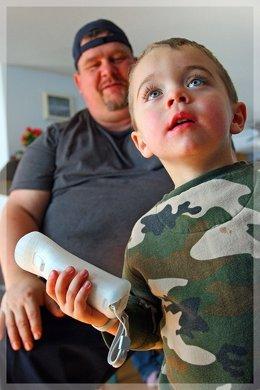 Niño jugando a la wii bajo la supervisión del padre