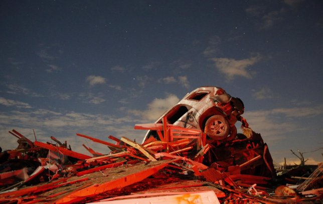 A vehicle sits on a pile of debris from the destruction caused by a tornado in W