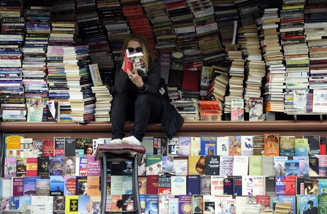 A woman reads a book at her open air book store in Skopje