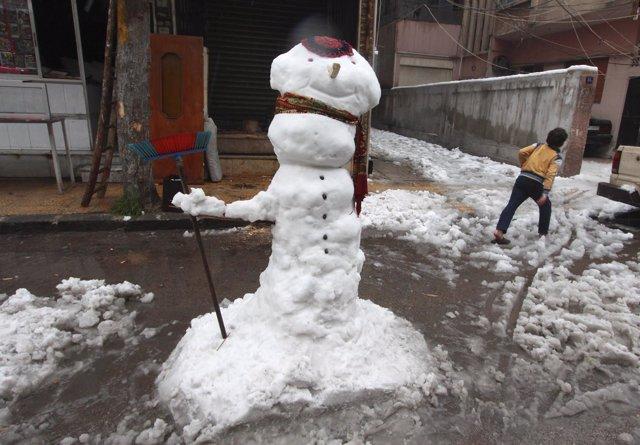Un niño junto a un muñeco de nieve en Damasco