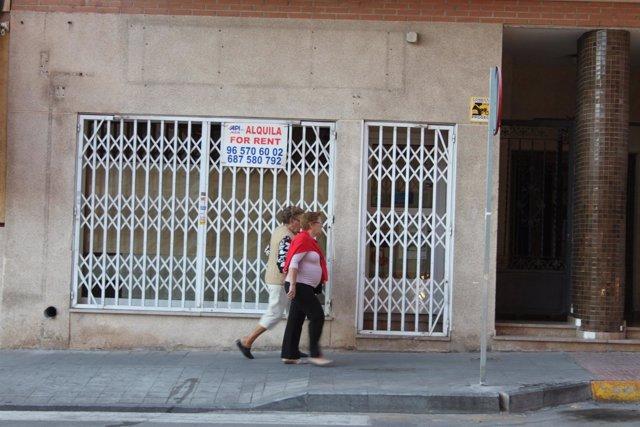 Dos mujeres pasan delante de un comercio cerrado en Torrevieja