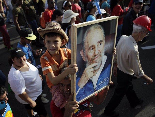 Un niño cubano sostiene un retrato de Fidel Castro
