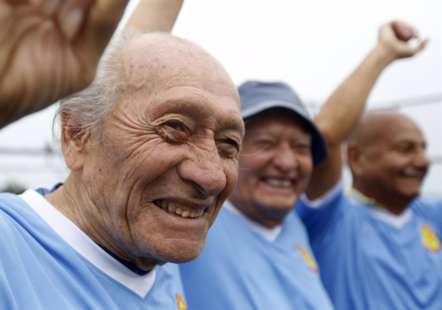 A group of senior soccer players pose for a picture after a match in Miraflores