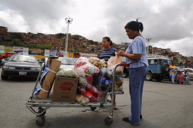 Customers stand with their purchases outside Makro supermarket in Caracas