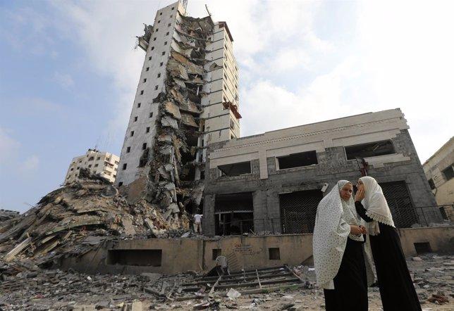 Mujeres palestinas junto a una torre bombardeada en Gaza