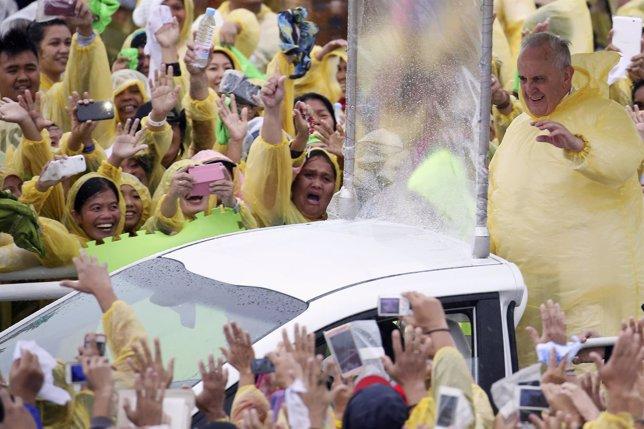 El Papa saluda a la multitud bajo la lluvia