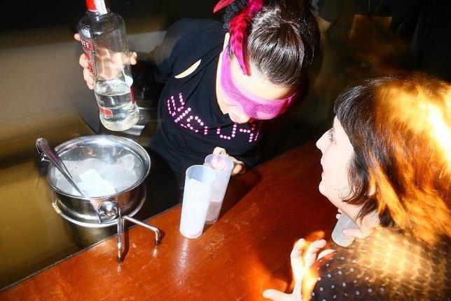 Chica pidiendo alcohol en la barra