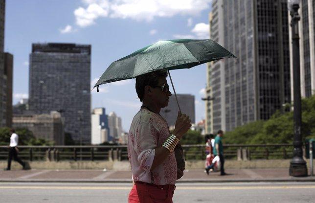 Un hombre se protege del sol con un paraguas en un día caluroso en Sao Paulo