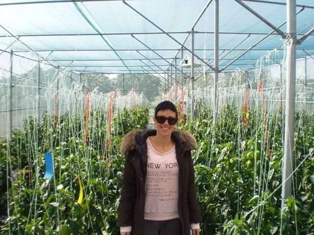 En la imagen, la autora de la tesis, en los invernaderos con malla