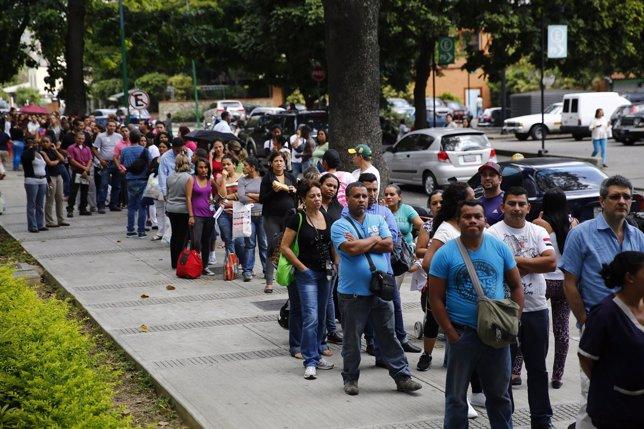 Personas hacen cola en un supermercado en Caracas